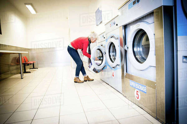 Woman using washing machine in laundrette Royalty-free stock photo