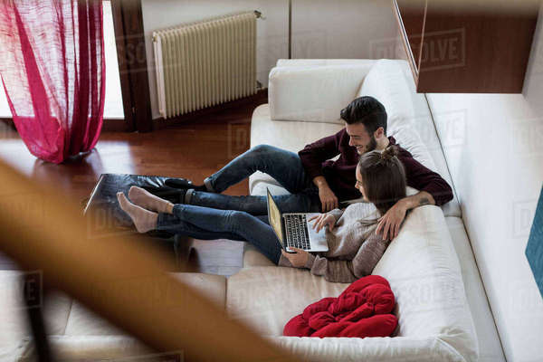 Young couple relaxing on sofa, looking at laptop, elevated view Royalty-free stock photo