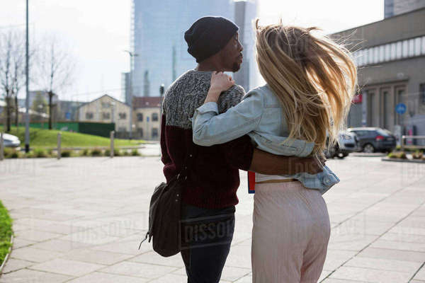 Young couple walking outdoors, arms around each other, rear view Royalty-free stock photo