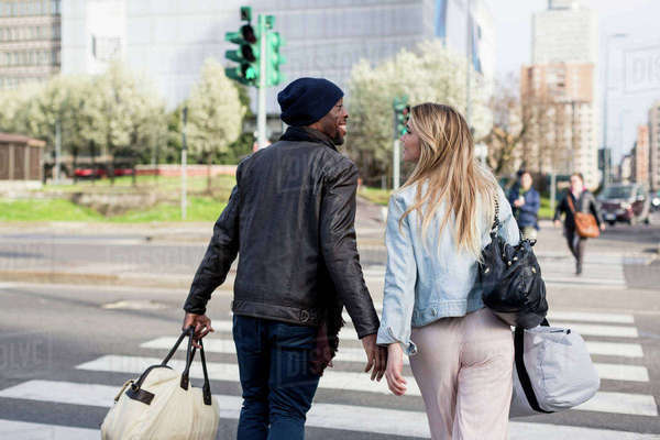 Young couple crossing road, carrying holdalls, rear view, smiling Royalty-free stock photo