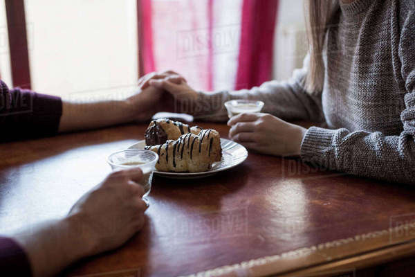 Couple sitting at table holding hands, holding coffee cups, pastries on table, close-up Royalty-free stock photo