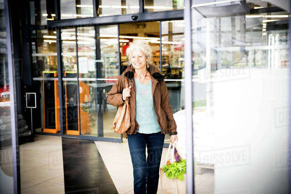 Mature woman exiting supermarket with bag of shopping Royalty-free stock photo