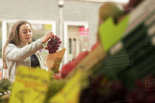Young woman buying bunch of grapes from market stall Royalty-free stock photo