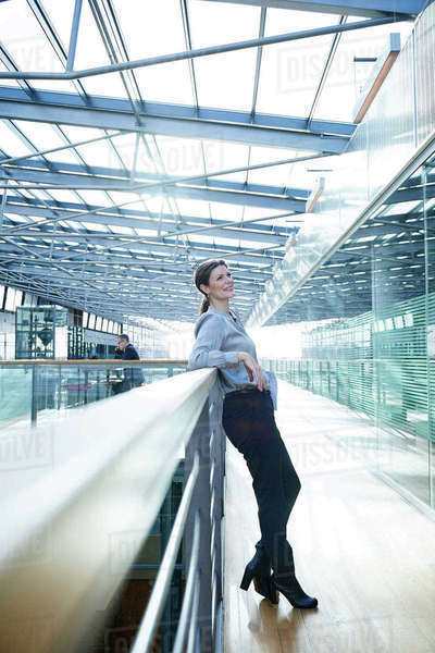 Happy businesswoman leaning against office balcony Royalty-free stock photo