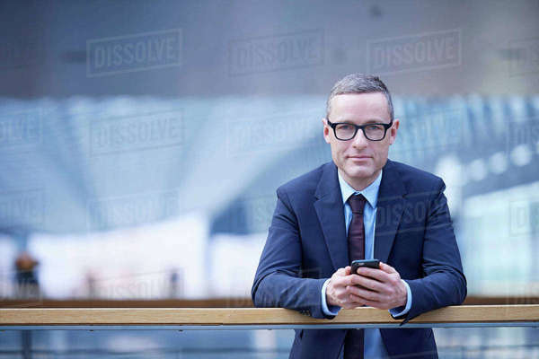 Portrait of businessman holding smartphone on office balcony Royalty-free stock photo