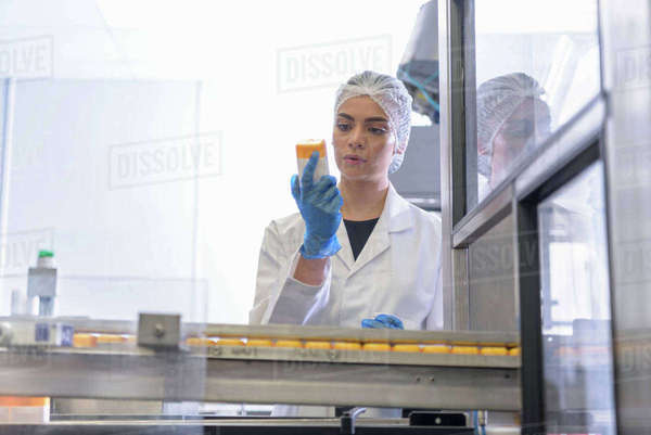 Female worker inspecting product in pharmaceutical factory Royalty-free stock photo