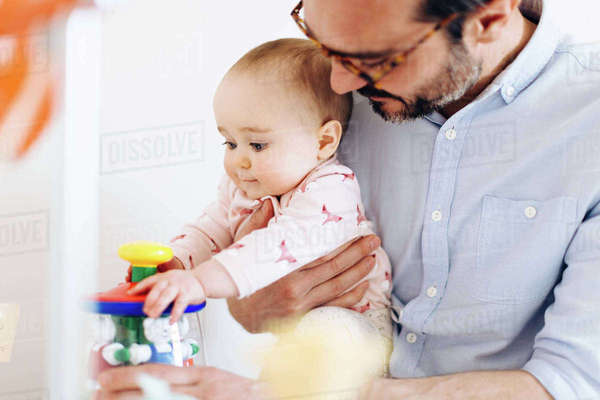 Father and baby daughter playing with toy Royalty-free stock photo