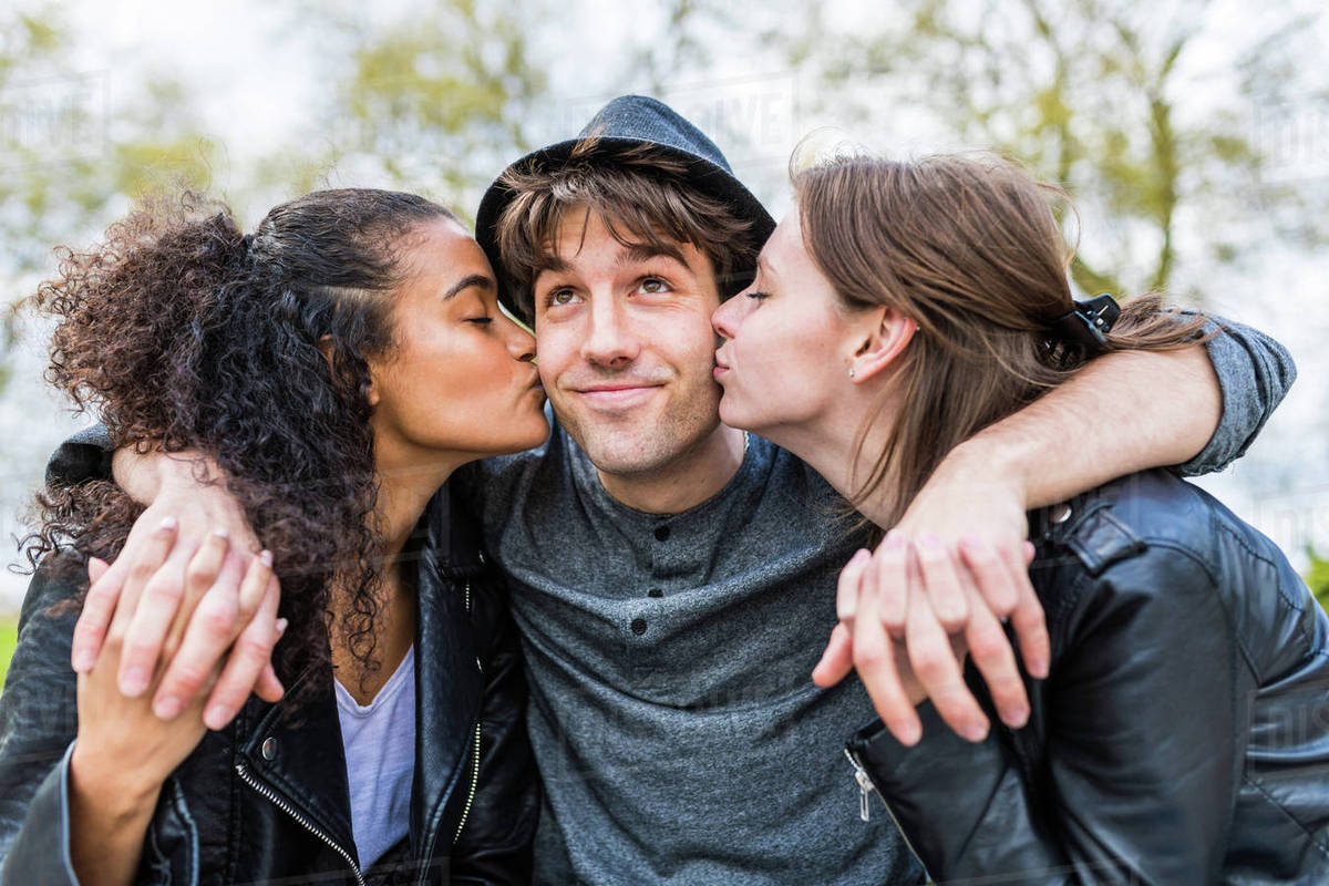 Young man between two women kissing him on cheek in Battersea Park
