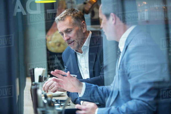 Two businessmen having discussion in restaurant window seat Royalty-free stock photo