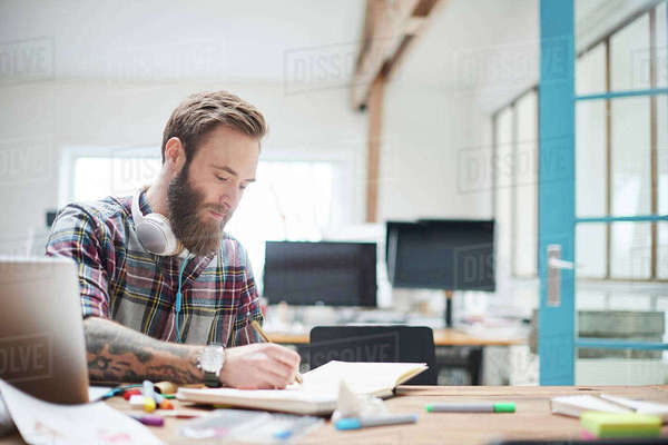 Young male designer writing notes at design studio desk Royalty-free stock photo