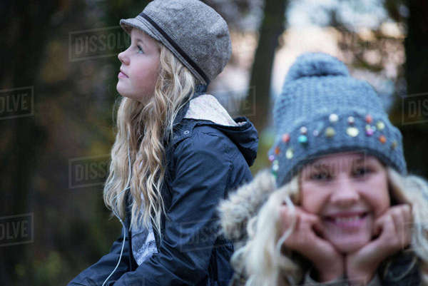 Portrait of girl and her sister in rural landscape wearing knit hat Royalty-free stock photo