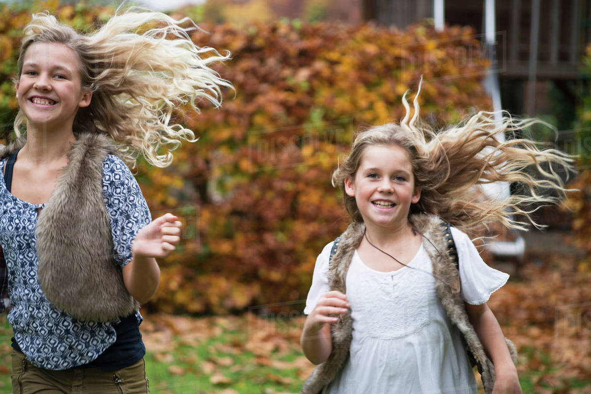 Two sisters with long blond hair running in autumn garden - Stock ...