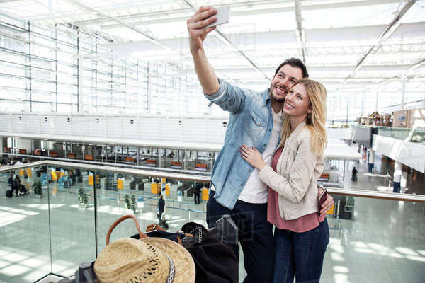 Young couple taking smartphone selfie in airport terminal Royalty-free stock photo