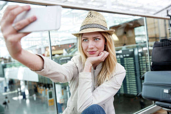 Young woman taking smartphone selfie in airport terminal Royalty-free stock photo
