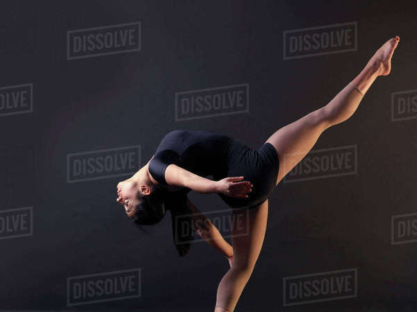 Low key shot of young female dancer bending backwards whilst standing on one leg Royalty-free stock photo