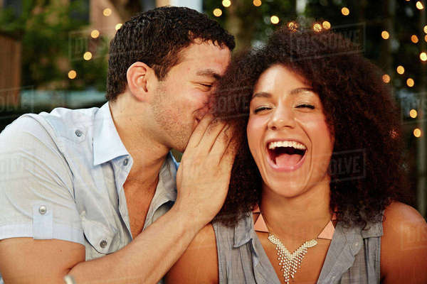 Young man whispering to laughing woman at garden party Royalty-free stock photo