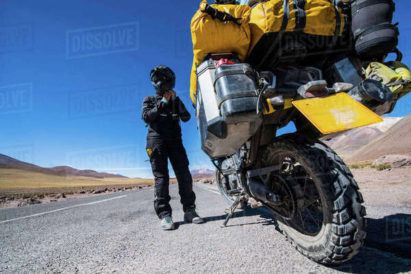 Woman standing next to touring motorbike on gravel road, Uyuni, Oruro, Bolivia, South America Royalty-free stock photo