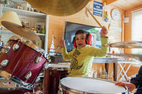 Boy wearing ear defenders playing drums Royalty-free stock photo