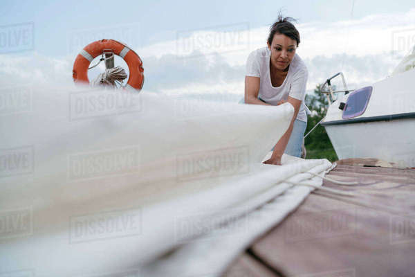 Young woman folding boat's sail Royalty-free stock photo