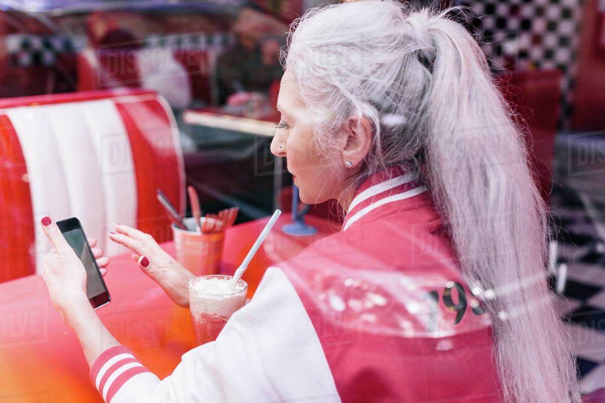 Mature woman in baseball jacket looking at smartphone in 1950's diner stock  photo