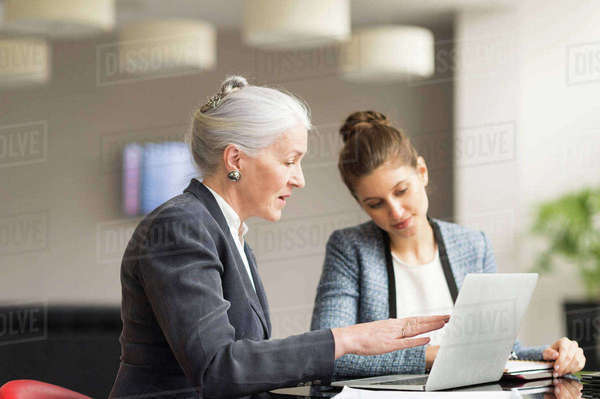 Businesswoman explaining to female colleague in boardroom meeting Royalty-free stock photo