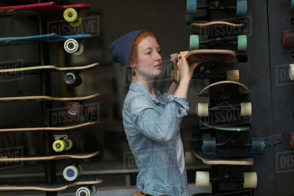 Woman working in skateboard shop, organising skateboard display Royalty-free stock photo