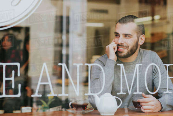Young man sitting in cafe, view through window Royalty-free stock photo