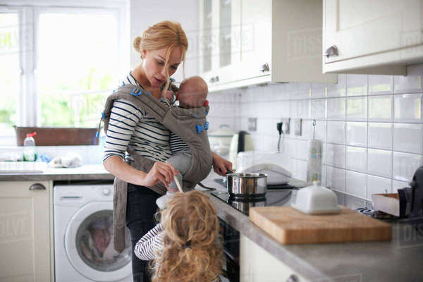 Woman cooking in kitchen, baby strapped to body in sling, daughter standing beside her Royalty-free stock photo