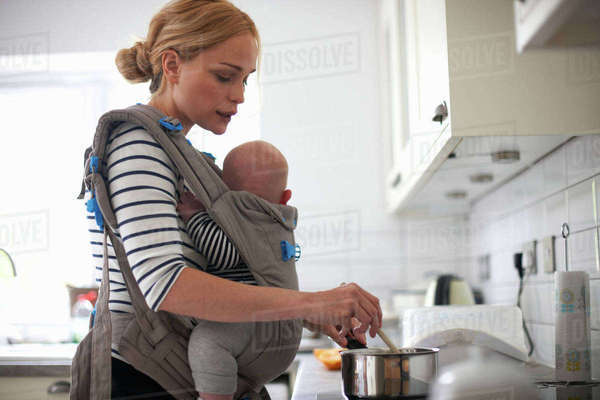 Woman cooking in kitchen, baby strapped to body in sling Royalty-free stock photo