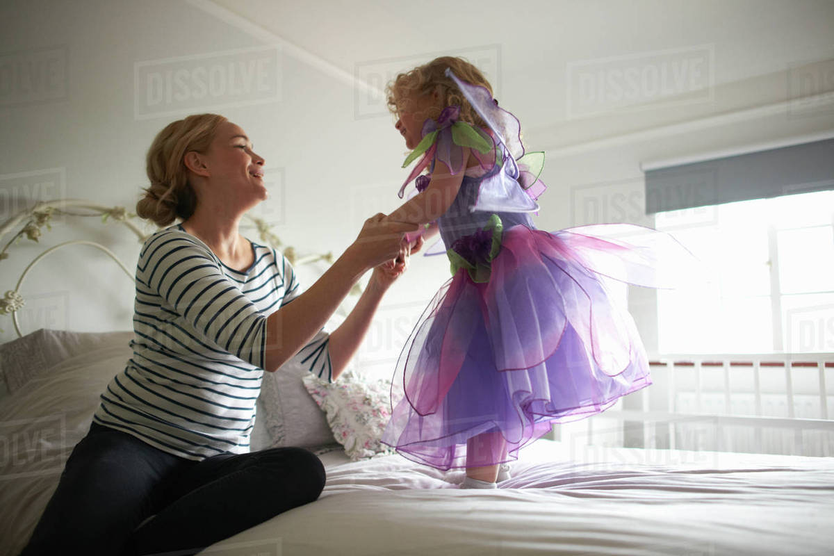 Young girl dressed in fairy costume, standing on bed, mother holding her hands Royalty-free stock photo