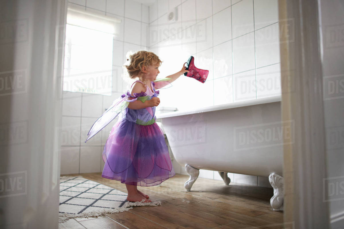 Young girl dressed in fairy costume, holding rubber boot over bathtub Royalty-free stock photo