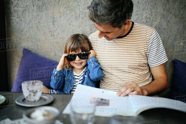 Girl playing with father's sunglasses in cafe Royalty-free stock photo
