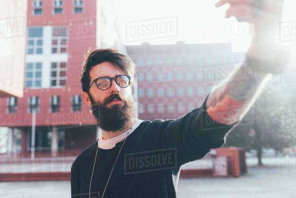 Cool young male hipster taking smartphone selfie in city Royalty-free stock photo