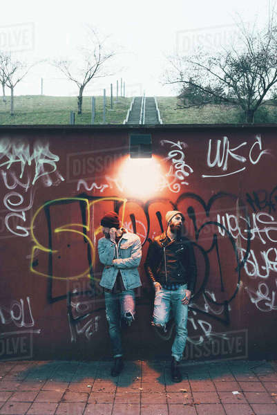 Portrait of two cool young male hipsters leaning against graffiti wall Royalty-free stock photo