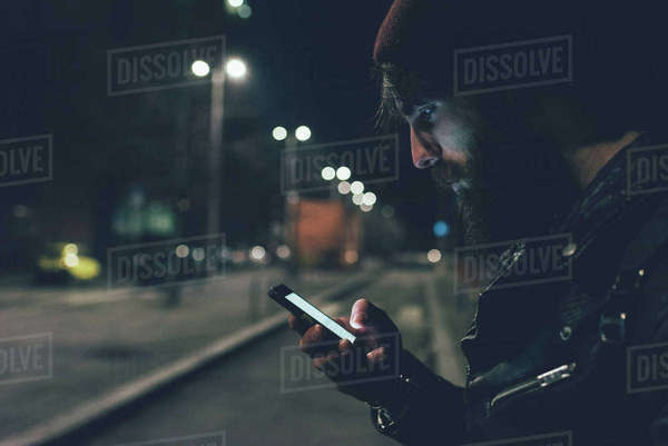Young male hipster on city street looking at smartphone at night Royalty-free stock photo
