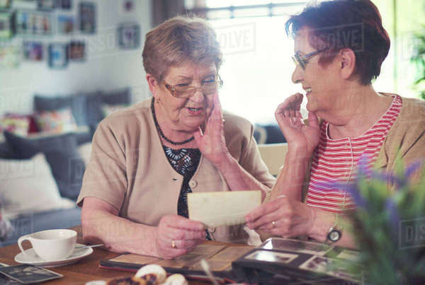 Two senior women chatting while looking at old photographs at table Royalty-free stock photo