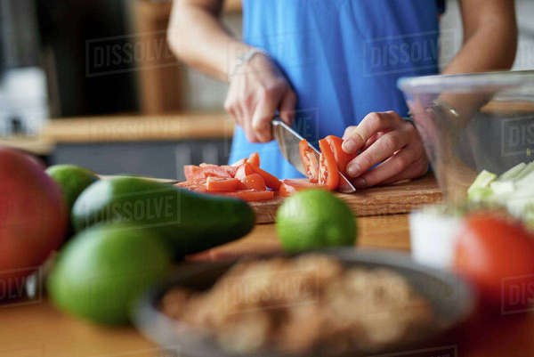 Hands of young woman at kitchen table slicing tomatoes Royalty-free stock photo