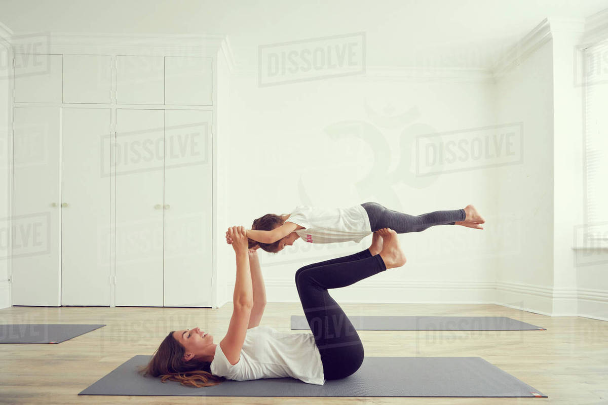 Mother And Daughter In Yoga Studio Daughter Balancing On Mothers Legs Stock Photo Dissolve