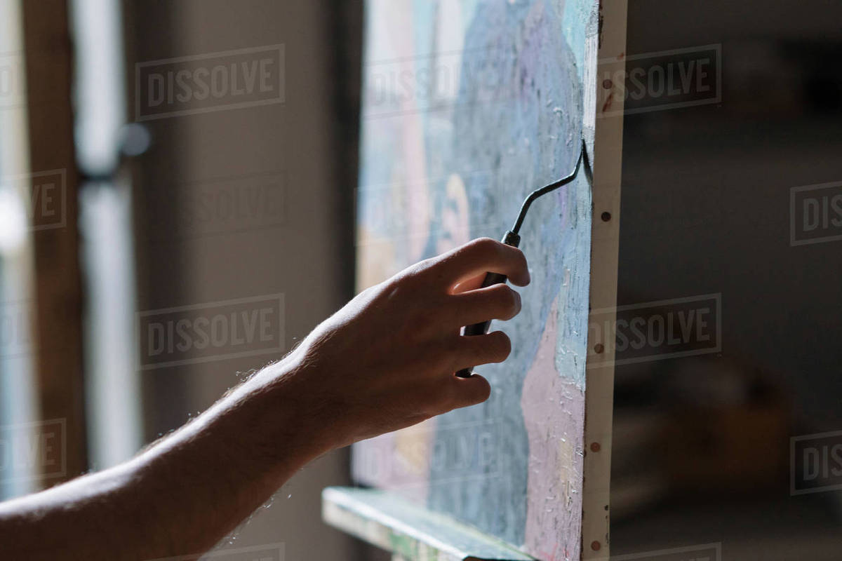 Male artist painting canvas in artists studio, detail of hand stock photo
