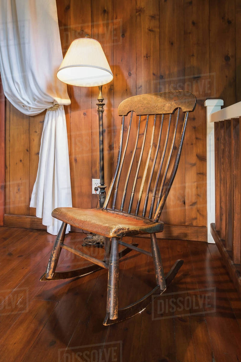 Antique wooden rocking chair and lamp, inside a New Hampton style home,  Quebec, Canada - Antique Wooden Rocking Chair And Lamp, Inside A New Hampton Style