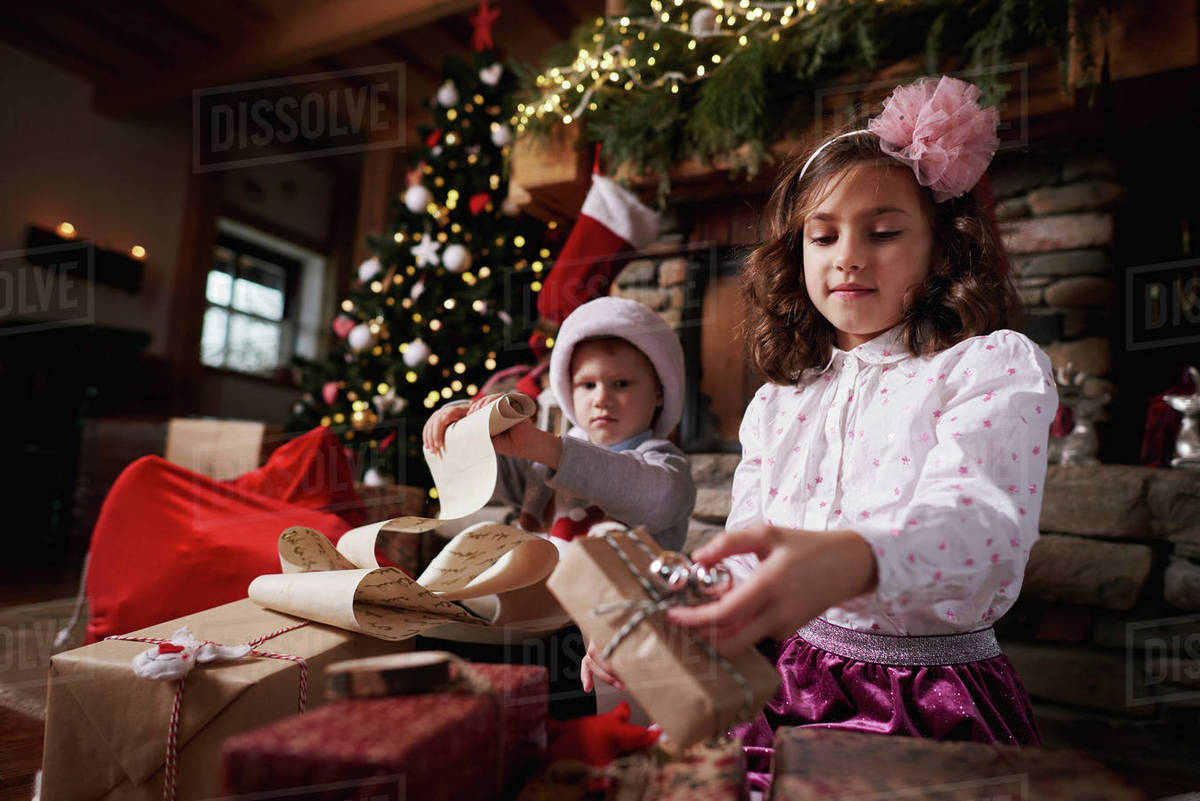 young girl and boy sorting christmas gifts young boy rolling list