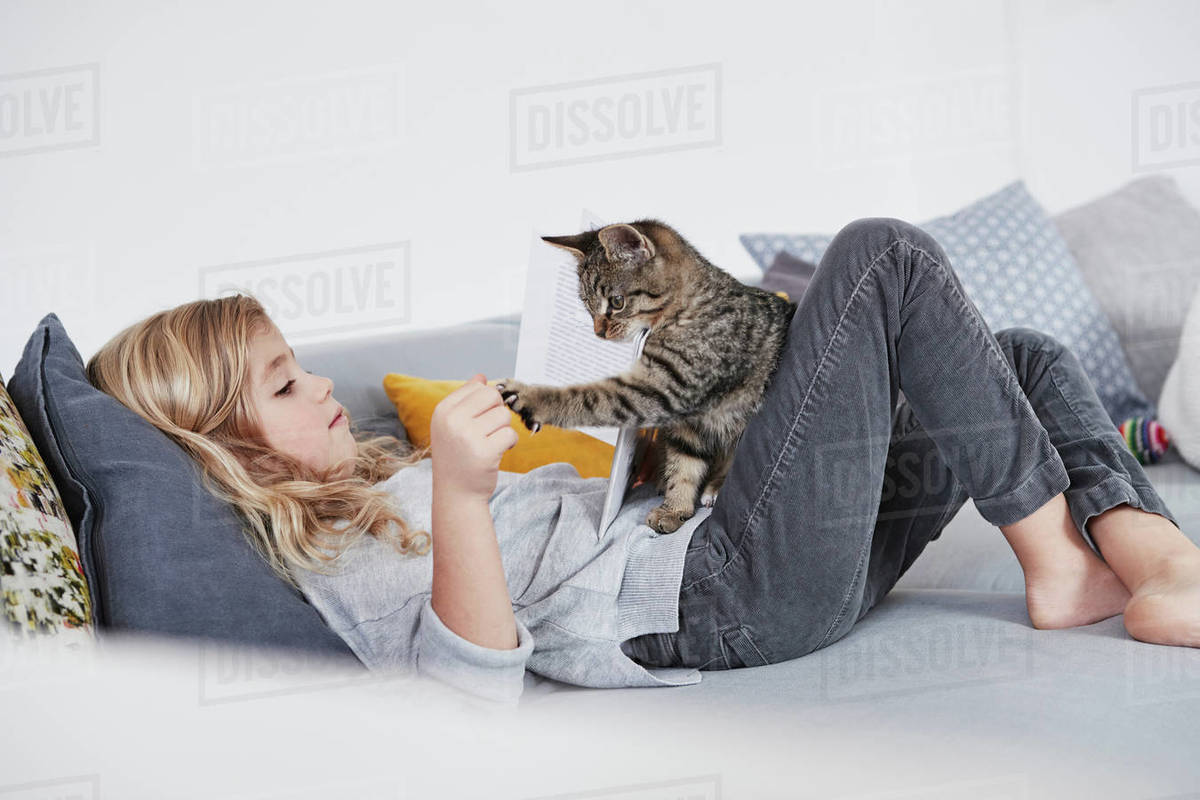 Young Girl Lying On Sofa, Playing With Pet Cat