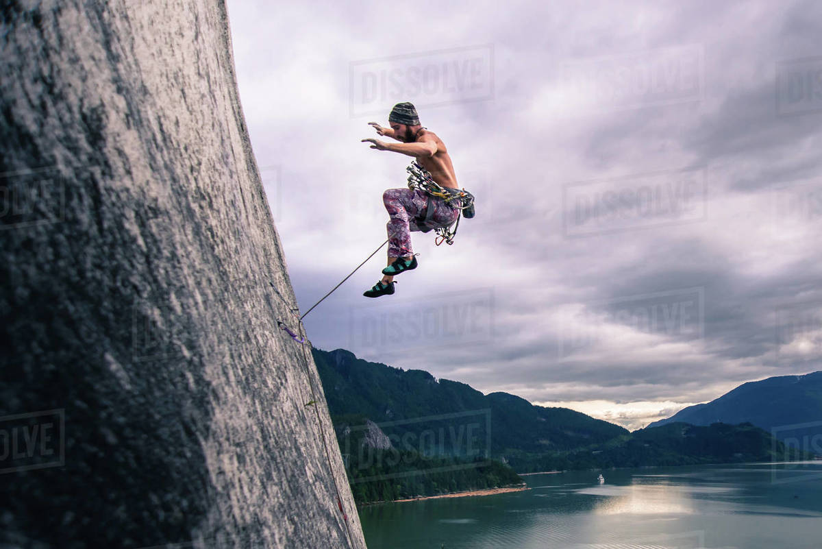 Man with climbing rope jumping off rock face on Malamute, Squamish, Canada Royalty-free stock photo