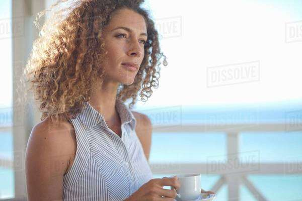 Young woman gazing out to sea from beach house balcony Royalty-free stock photo
