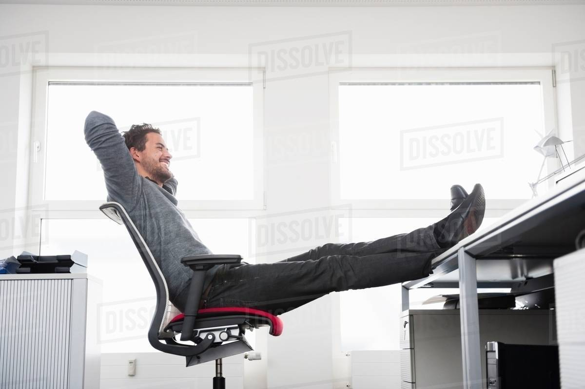 Man Sitting On Office Chair With Feet Up Desk