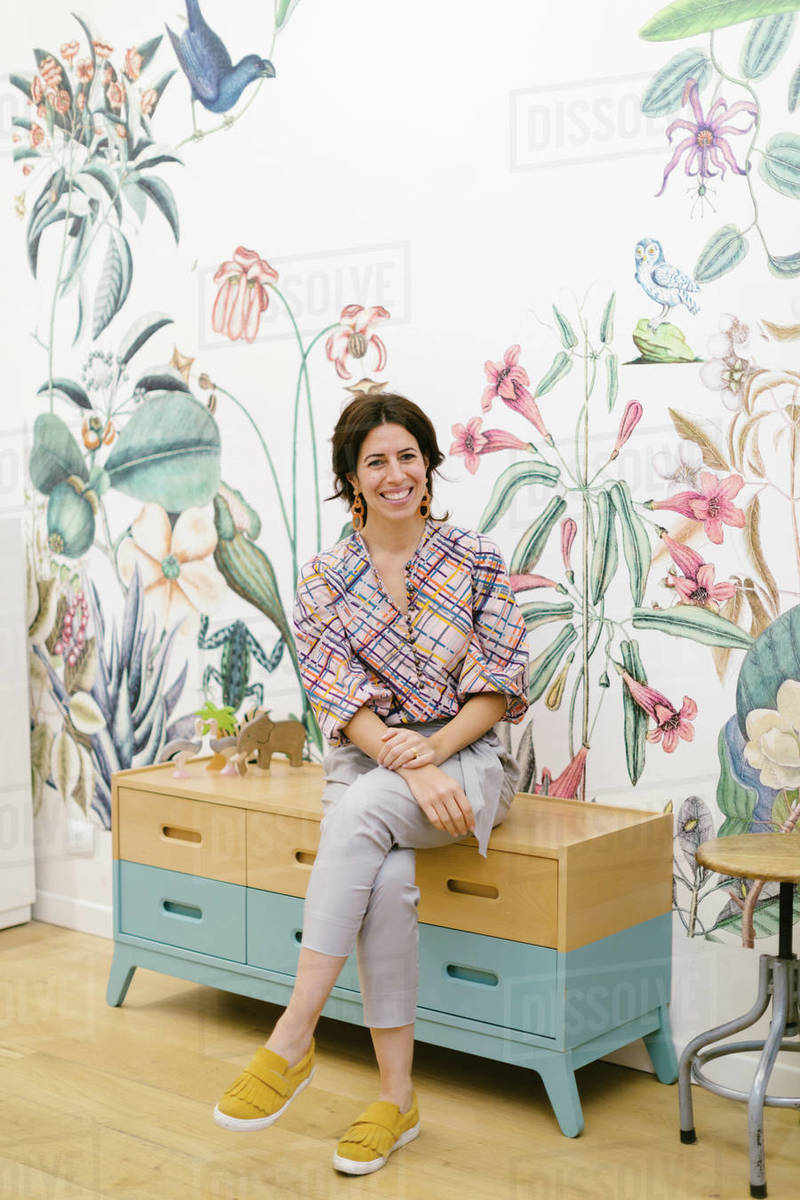 Woman Sitting On Cabinet Floral Pattern Wallpaper In Background Stock Photo