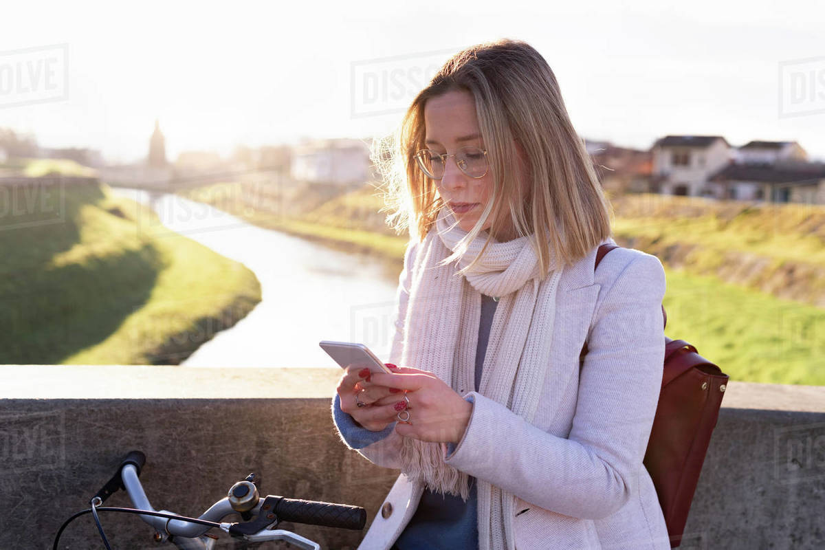 Female higher education student on river bridge looking at smartphone, Florence, Italy Royalty-free stock photo