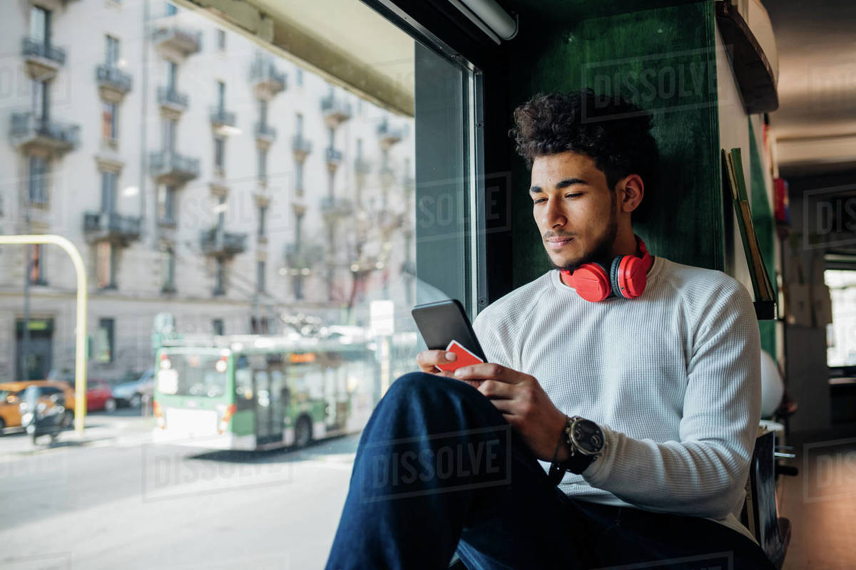 Young man looking at smartphone in cafe window seat Royalty-free stock photo
