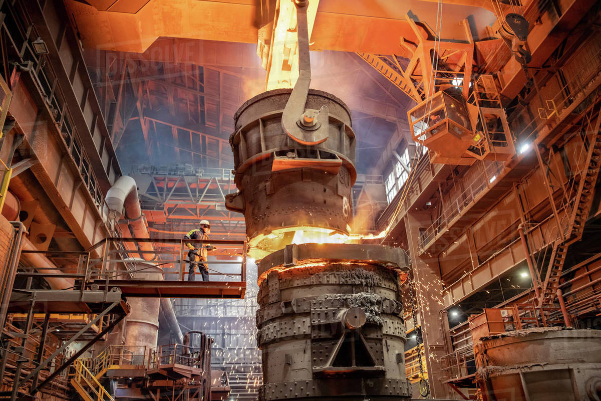 Steelworker starting molten steel pour in steelworks Royalty-free stock photo