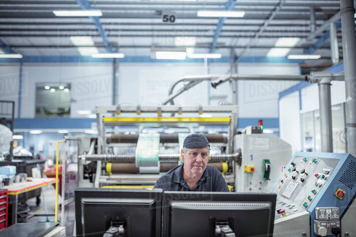 Worker inspecting screen in print factory Royalty-free stock photo
